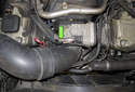 Working at the throttle housing duct, loosen the hose clamp using a flathead screwdriver (green arrow).