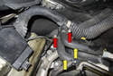 Working at the right rear of the engine, remove the oil separator hoses (yellow arrows).