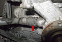 Working at the bottom right side of the water pump, use a flathead screwdriver to lever out the coolant hose retaining clip (red arrow).