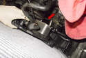 Remove the transmission cooler bracket with the cooler to the left, removing it through the gap between the crankshaft pulley and power steering pump (red arrow).