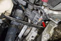 Use a 19mm wrench (red arrow) to loosen the tensioner.