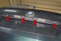 Tailgate release handle: To remove the handle, start by removing the four T20 Torx fasteners (red arrows).