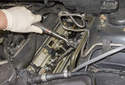 """Using a 5/8 thin-wall spark plug socket on a 12"""" extension, remove the spark plug from the cylinder head."""