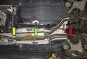 The driveshaft runs through the transmission tunnel from the transmission (yellow arrow) to the rear differential (red arrow) supported by the center bearing (green arrow).