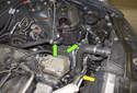 Working at the side of the coolant expansion tank, locate the two lower coolant hoses (green arrows).