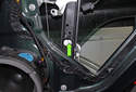 Lower the glass down until the bolt is accessible through the opening (green arrow) in the window regulator.