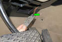 Working in the driver's footwell, remove the courtesy light from the lower dashboard trim panel and disconnect the wiring harness (green arrow).