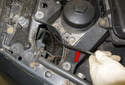 Pull the cable out of the radiator support (red arrow) and detach it from the union.