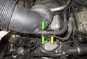 Working at the bottom of the intake air duct, detach the plastic line by squeezing the release collar (green arrows) while pulling the line off the duct.