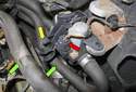 To replace the heater control valve, start by removing the heater hoses (green arrows) from the plastic mount (yellow arrow).