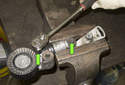 A/C belt tensioner: To replace the tension strut, remove both 13mm fasteners (green arrows).
