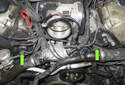 The VANOS solenoids are located at the front timing cover of each bank of the engine (green arrows).