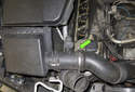 Working at the mass air flow sensor, loosen the hose clamp using a flathead screwdriver (green arrow).