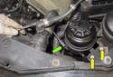 Working at the power steering reservoir, loosen the 10mm clamping bolt (green arrow).