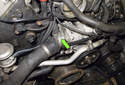 The thermostat is located at the front of the engine, just above the water pump (green arrow).
