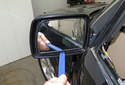 Mirror glass replacing: Using a plastic prying tool, gently lever out the mirror glass by prying from the bottom center .