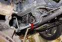 With the axle removed, inspect the drive axle seal for damage or signs of leaking and replace if needed (red arrow).