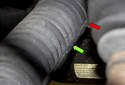 Next, use pliers or a flathead screwdriver (green arrow) and remove the inner boot clamp (red arrow).