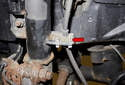 Working at the front strut, remove the brake hose mounting clip (red arrow).