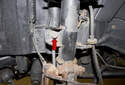 Working at the front strut, remove the stabilizer link nut (red arrow).