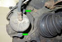Remove the rubber plugs from the brake caliper mounting fasteners (green arrows).