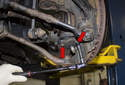 Working at the ball joint, remove both E12 fasteners (red arrows).