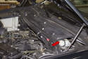 The brake master cylinder is located below the wiper cowl trim (red arrow) on the left side of the vehicle.