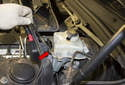 Using a 12mm line wrench, loosen the top brake line (red arrow).
