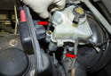 Pull both brake lines out of the master cylinder (red arrows).