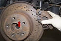 Then, remove the brake caliper and secure it in place using a stiff wire.