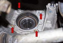 Working at back of wheel bearing carrier, remove the four E14 wheel bearing fasteners (red arrows).