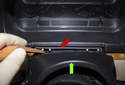 Working at the top of the steering column trim panel, lever the flexible trim (red arrow) off the steering column (green arrow) upward, using a plastic prying tool.