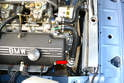 The thermostat is located on the right front of the engine and is connected to three hoses (red arrow).