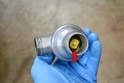 This photo illustrates how the thermostat is contained within the housing and must be replaced as a unit (red arrow).