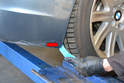 Use your trim removal tool to remove the plastic push/pull pin connecting the wheel well liner to the cover (red arrow).