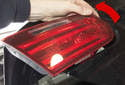 Lift inner edge of tail light up and remove at an angle (red arrow), unhooking it from the trunk lid.