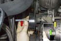 Unscrew and remove the idler pulley from the engine with the long bolt (red arrow).