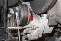 A/C belt tensioner: Using a 13mm socket, remove the upper tensioner mounting fastener.