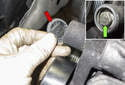 Accessory belt tensioner: Working at the top of the tensioner, remove the dust cap (red arrow).