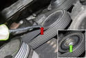 Accessory belt tensioner: Remove the tensioner pulley dust cap (red arrow).