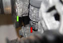Accessory belt tensioner: Working below the pulley mounting bore (green arrow), remove the 13mm tensioner mounting fastener (red arrow).