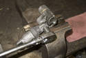 Accessory belt tensioner: Secure the tensioner in the vise.