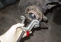 Using a hub puller (red arrow), remove the wheel bearing with the flange.