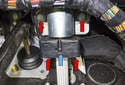 Working at the base of the steering column, remove the four 13mm fasteners (red arrows).