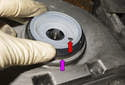 Place the seal with sleeve (purple arrow) onto to the crankshaft and align the pin (red arrow) into the drilled hole.