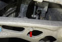 Working at the bottom of the right front control arm, remove the 13mm nut (red arrow).
