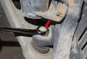 Working at the steering knuckle, remove the 18mm ball joint nut (red arrow).
