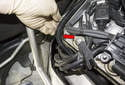 Working at the rear corner of the cylinder head, pull the wiring harnesses (red arrow) out of the heat shield.