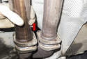 Slide the front pipe toward the rear of the vehicle to detach it from the headers (red arrow).