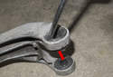 To replace the transmission insulating bushings, use a flathead screwdriver and lever the bushing in and down (red arrow) to remove.